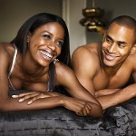 young black male and female laughing together on bed